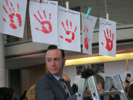 Lars Möller, Mitarbeiter der Kinderkommission, beim Aufhängen der Handabdrücke