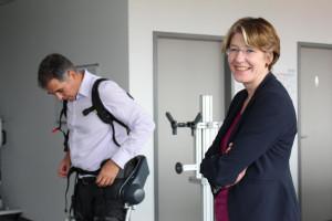 CEO Dr.-Ing. Peter Heiligensetzer mit Exoskelett, MdB Ulrike Bahr.